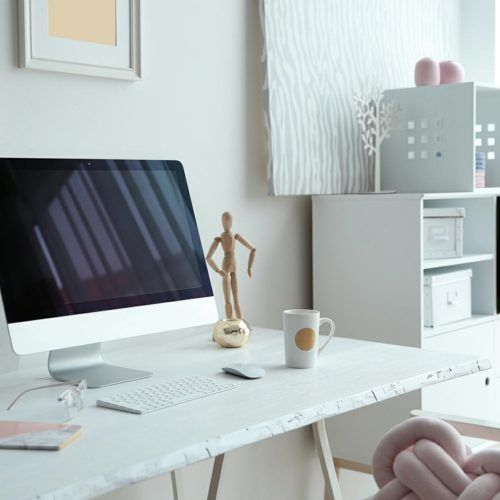 Contemporary workplace with computer on table near white wall. Interior design